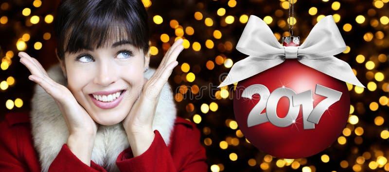 La donna con la palla rossa di Natale, sorridendo e cerca sulle luci royalty illustrazione gratis