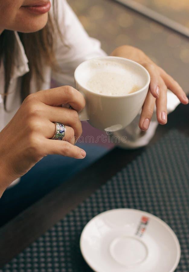 La donna con le belle mani sta bevendo il caff? in caff? Cappuccino del primo piano in tazza bianca, immagine con l'elaborazione  fotografia stock