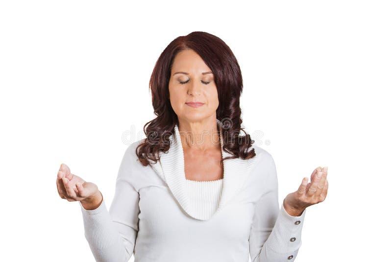 La donna con le mani chiuse degli occhi si è alzata nel meditare dell'aria immagine stock libera da diritti