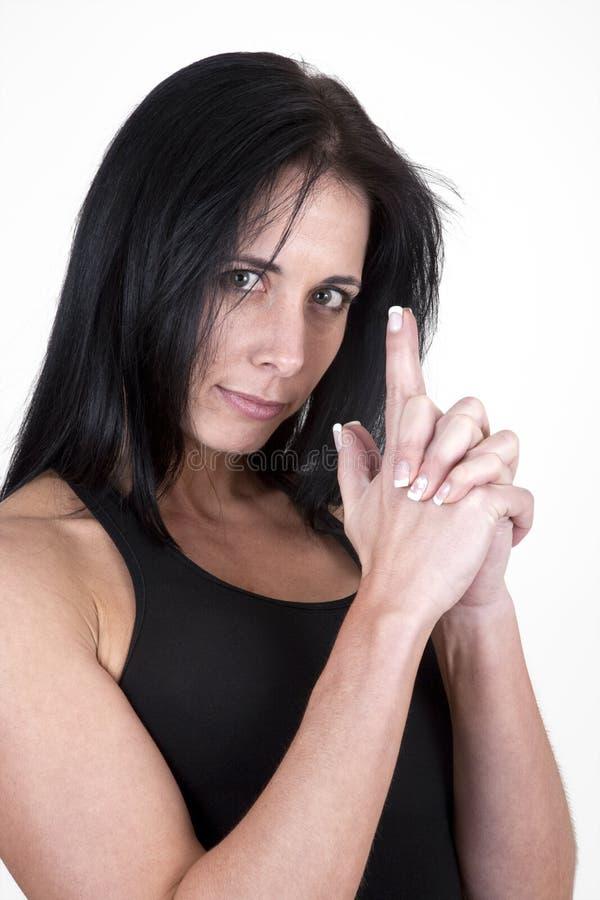 La donna con le sue mani ha modellato come una pistola fotografia stock libera da diritti