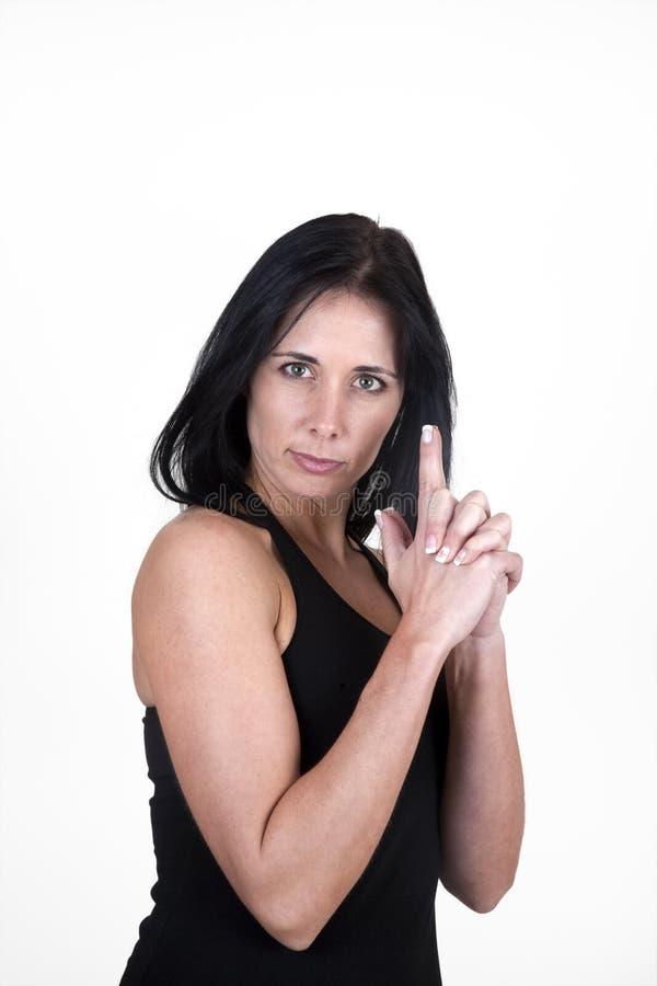 La donna con le sue mani ha modellato come una pistola immagine stock libera da diritti