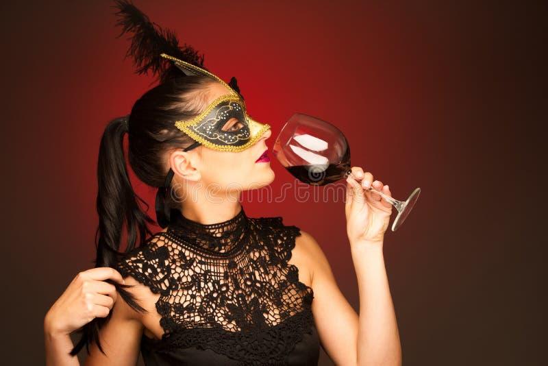 La donna con la maschera di Venezia e un bicchiere di vino per il carnevale fanno festa fotografie stock