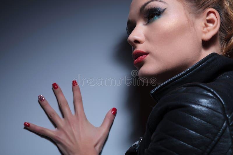 La donna con piacevole compone e le unghie rosse manicure, spingendo il wal immagini stock libere da diritti