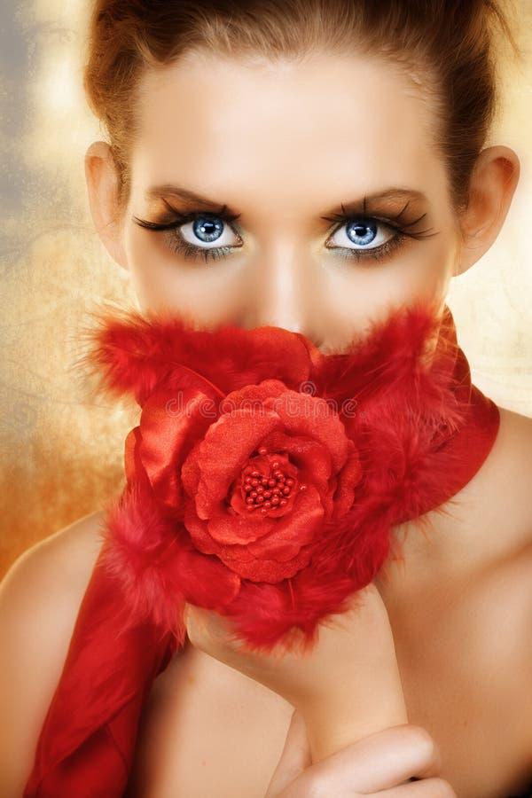 La donna con seta rossa è aumentato fotografia stock