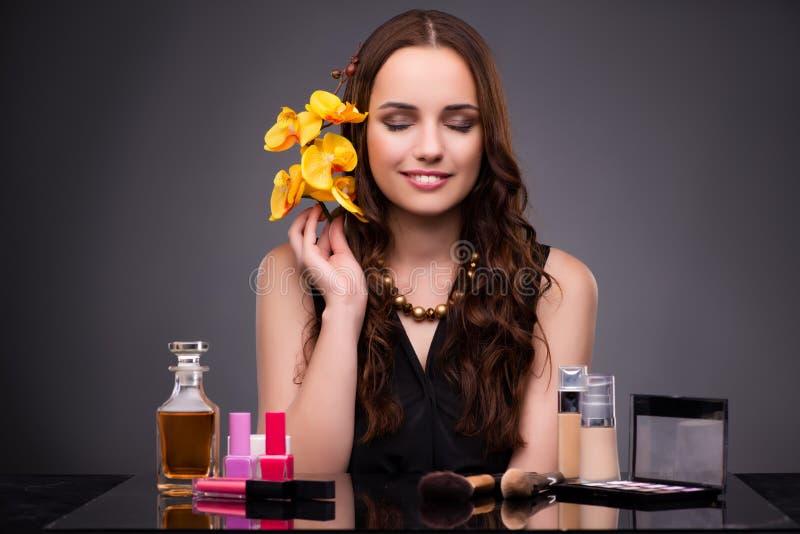 La donna con trucco ed il fiore dell'orchidea fotografia stock