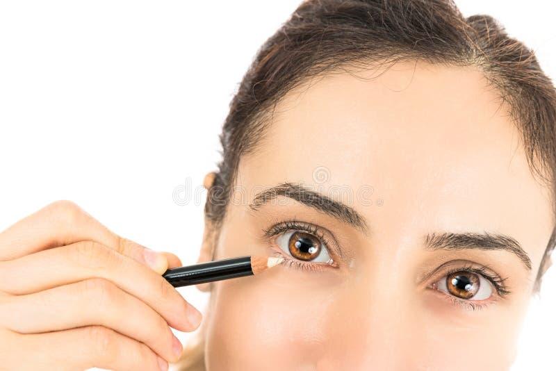 La donna con un eye-liner che applica l'occhio compone fotografia stock