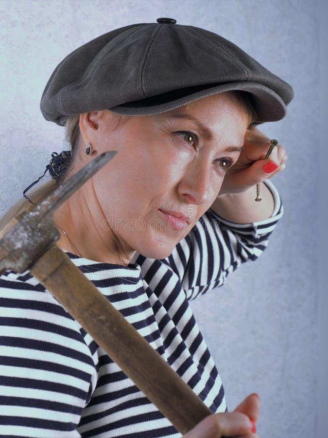 La donna con un martello immagine stock