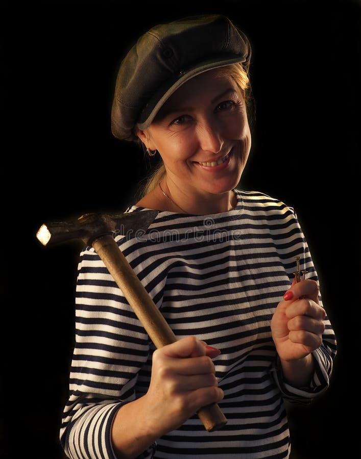 La donna con un martello fotografia stock