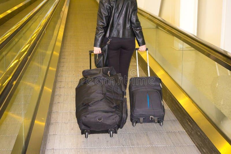 La donna con valigie che cammina alla scala mobile all'aeroporto immagine stock