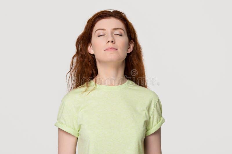 La donna conscia calma della testarossa che prende la respirazione profonda si sente libero fotografie stock