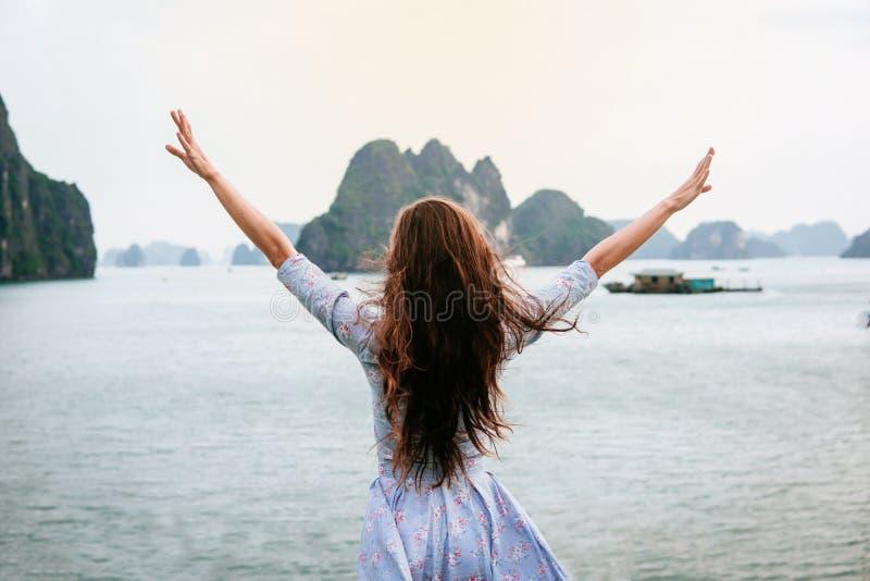 La donna considera la baia di HALONG nel Vietnam ed aumenta mani Luogo del patrimonio mondiale dell'Unesco fotografia stock