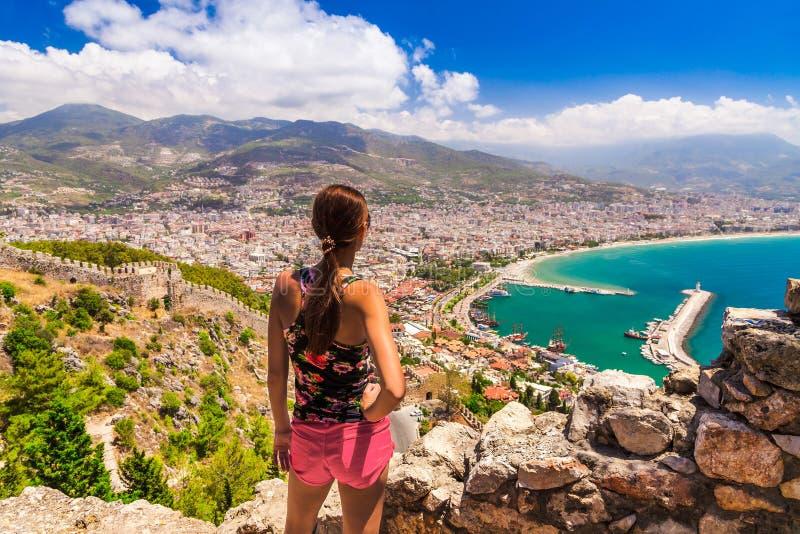 La donna considera il paesaggio di Alanya con il porticciolo e la torre rossa di Kizil Kule nel distretto di Adalia, Turchia, Asi immagini stock libere da diritti