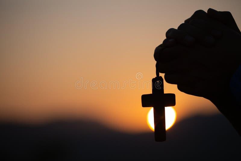 La donna cristiana che prega sull'incrocio santo di mattina, mano della donna dell'adolescente con l'incrocio che prega, mani ha  fotografie stock libere da diritti