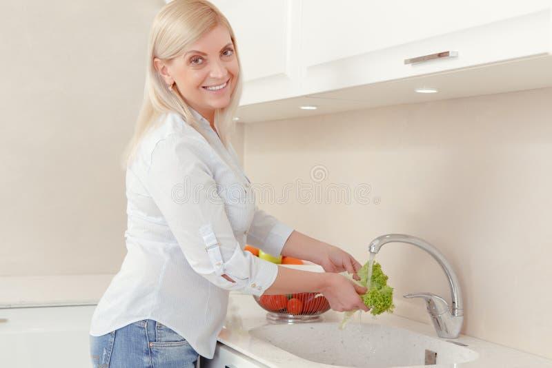 La donna cucina l'insalata per pranzo immagini stock