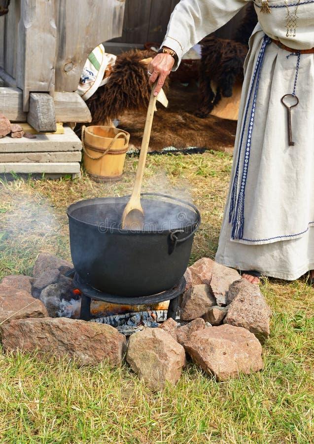 La donna cucina la bevanda medica su un fuoco immagini stock