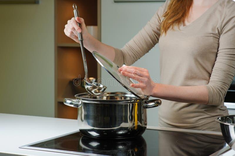 La donna cucina la minestra nella cucina fotografie stock