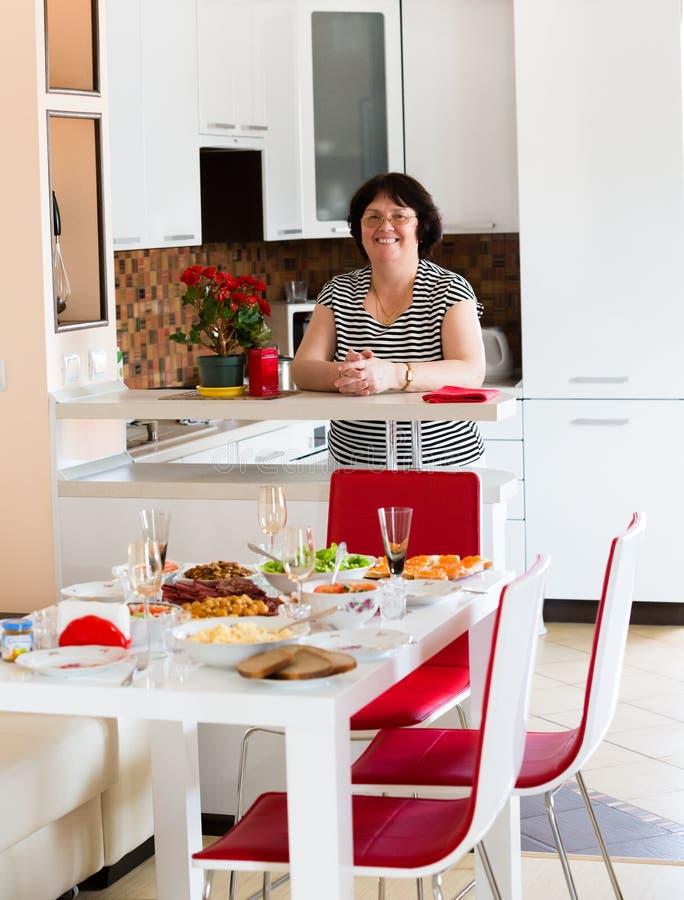 La donna in cucina sta aspettando gli ospiti immagini stock libere da diritti