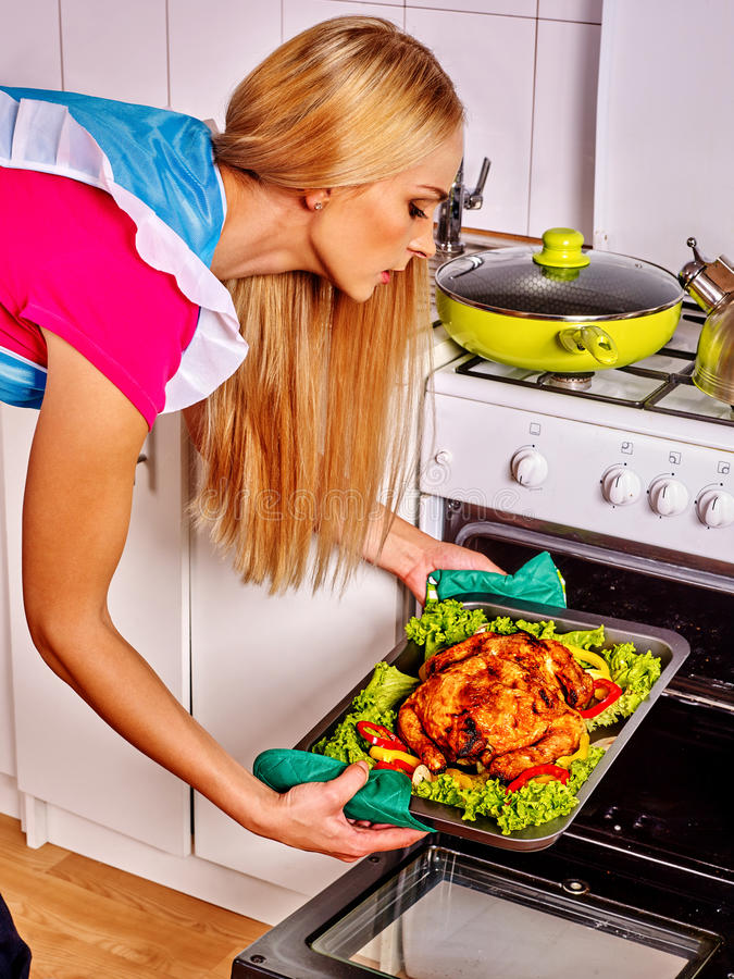 La donna in cucina sta cucinando l'alimento della carne dell'arrosto in forno immagine stock
