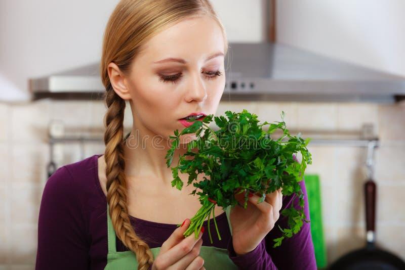 La donna in cucina tiene il prezzemolo aromatico verde immagine stock libera da diritti