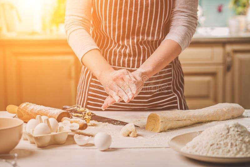 La donna cuoce le torte Il confettiere produce i dessert Produrre i panini Pasta sulla tavola Impasti la pasta fotografia stock