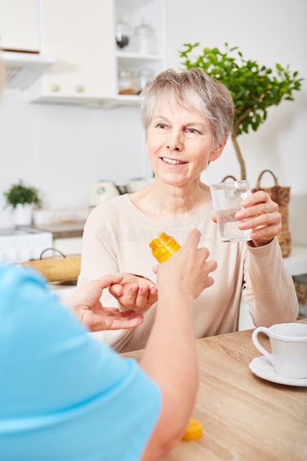 La donna dà il farmaco senior fotografie stock