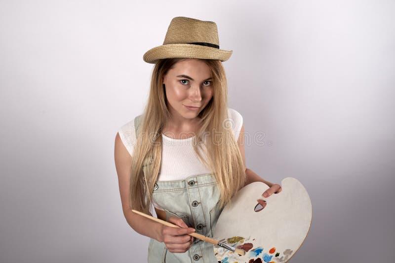 La donna dai capelli lunghi attraente in un cappello del vestito e della luce dal denim fa soffrire immagine stock
