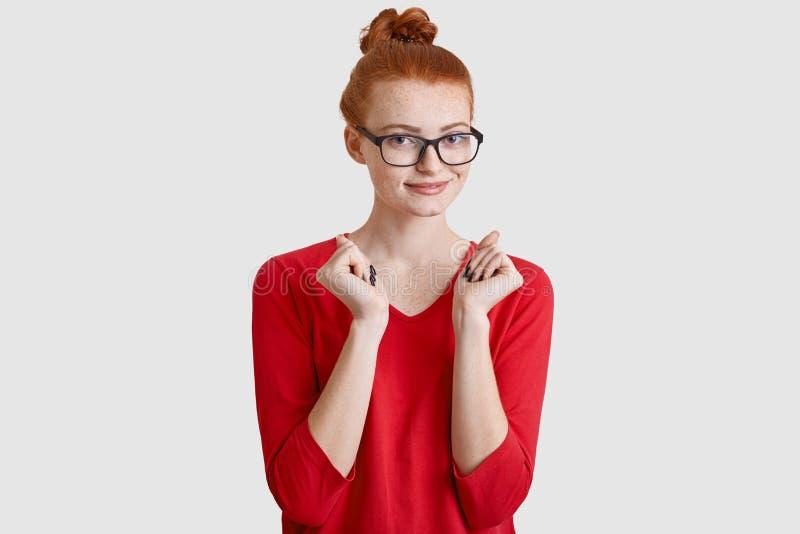 La donna dai capelli rossi piacevole con il nodo dei capelli, indossa i vetri trasparenti, tiene consegna il petto, vestito in sa fotografia stock