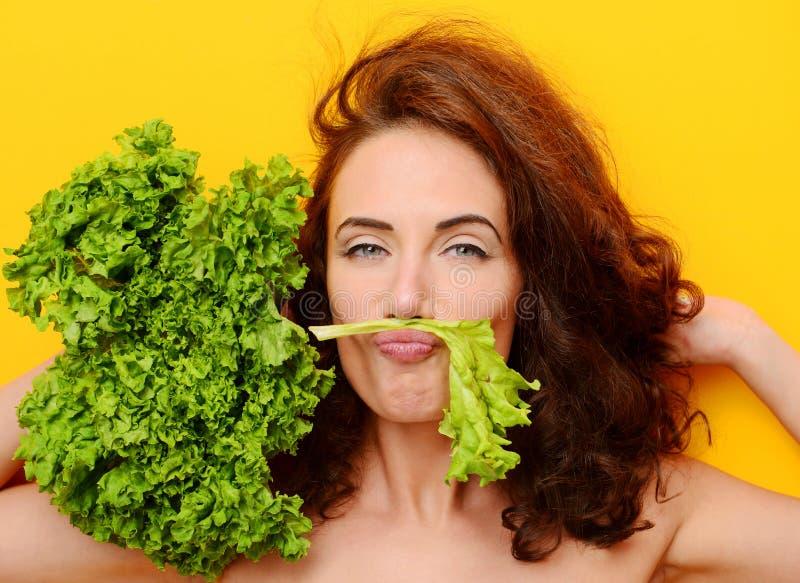 La donna dei capelli abbastanza ricci mangia l'insalata della lattuga che esamina l'angolo su fondo giallo fotografia stock libera da diritti