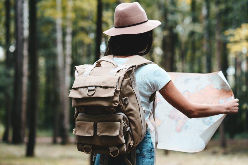 La donna dei pantaloni a vita bassa del viaggiatore con lo zaino ed il cappello tengono in mani tracciano e cercando il modo fra  immagine stock