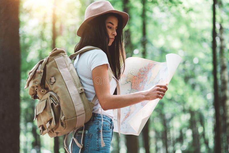 La donna dei pantaloni a vita bassa del viaggiatore con lo zaino ed il cappello tengono nella mappa e nella ricerca di posizione  fotografia stock