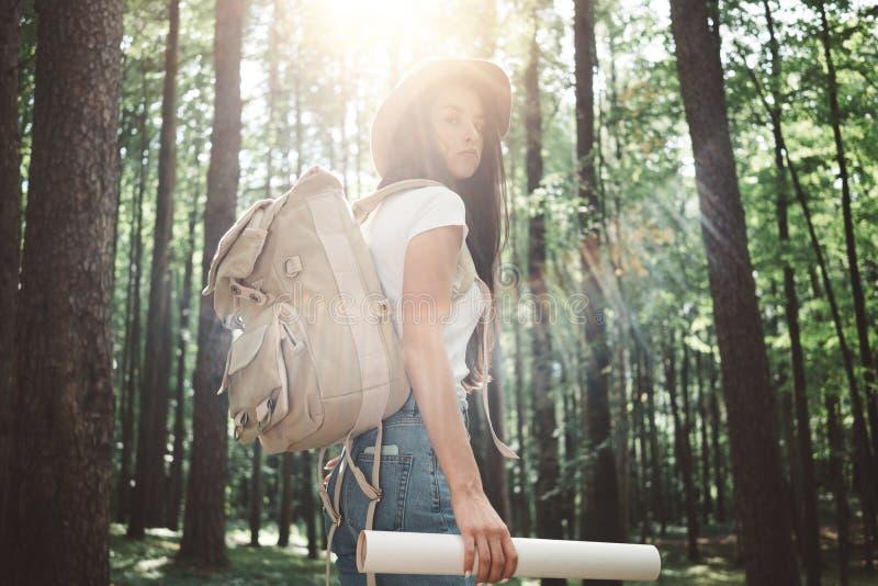 La donna dei pantaloni a vita bassa del viaggiatore con lo zaino ed il cappello tengono nella mappa e nella ricerca di posizione  fotografie stock libere da diritti