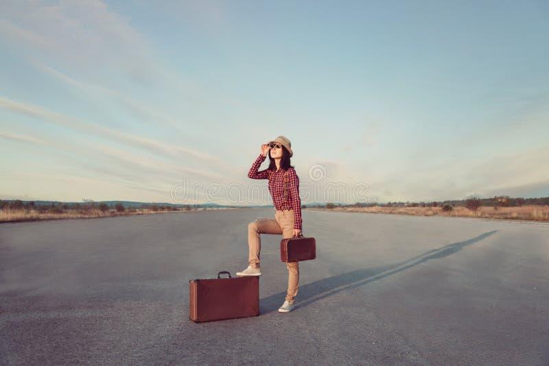 La donna dei pantaloni a vita bassa del viaggiatore guarda tramite il binocolo immagini stock libere da diritti