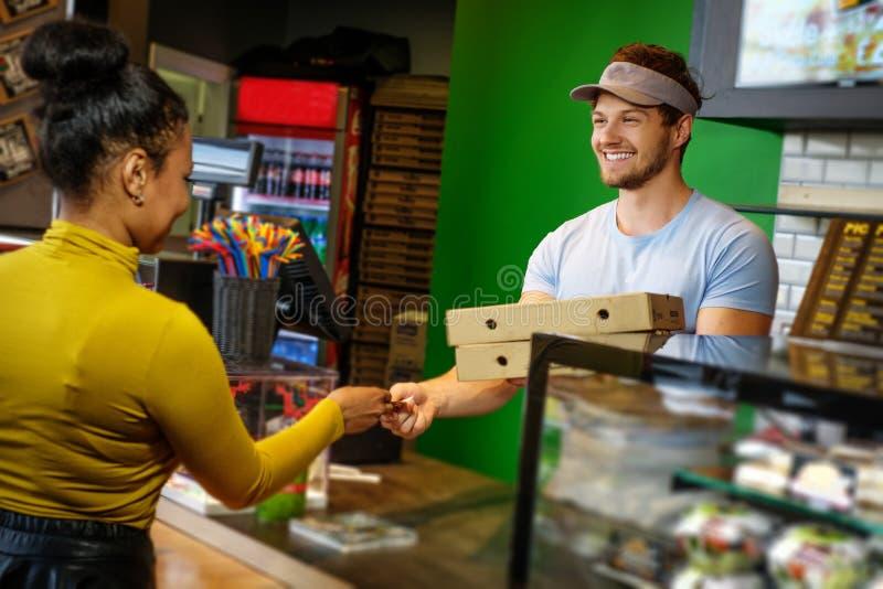 La donna del cliente prende al suo ordine nella pizzeria immagine stock libera da diritti