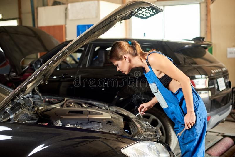 La donna del meccanico dà una occhiata a sotto il cappuccio dell'automobile nera immagine stock