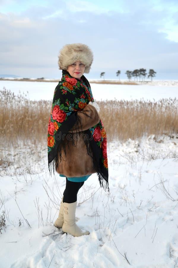 La donna del medio evo in un cappuccio della pelliccia ed in uno scialle variopinto costa sulla banca del lago dell'inverno fotografia stock