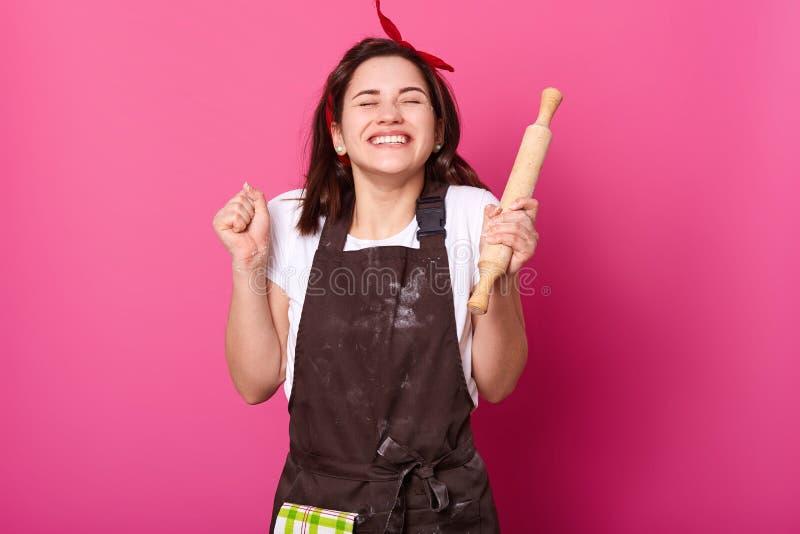 La donna del panettiere tiene il matterello bollente, indossa il grembiule marrone, maglietta bianca La ragazza piega i gomiti e  fotografia stock libera da diritti