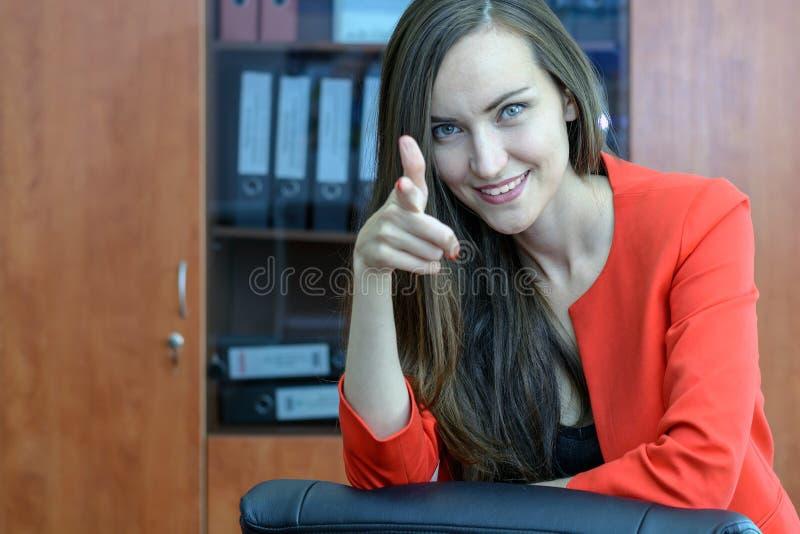 La donna del ritratto inizia la sua giovane impresa, esaminando la macchina fotografica ed i punti un dito voi il concetto dell'i fotografia stock libera da diritti