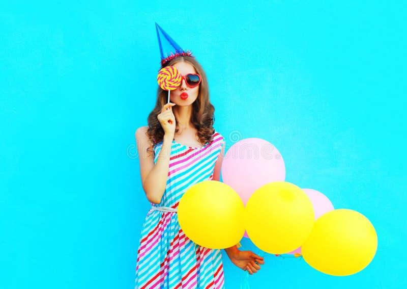 La donna del ritratto in un cappuccio di compleanno tiene un'aria che i palloni variopinti sta soffiando le labbra è chiude il su fotografia stock