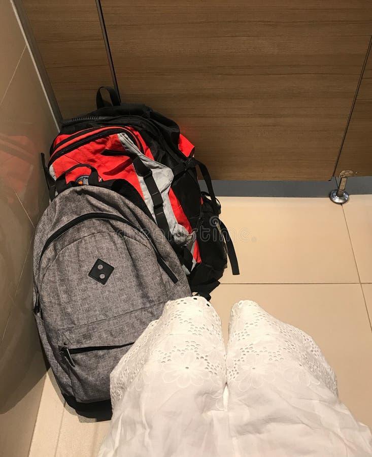 La donna del viaggiatore che si siede sulla toilette con la sua borsa imballa fotografia stock