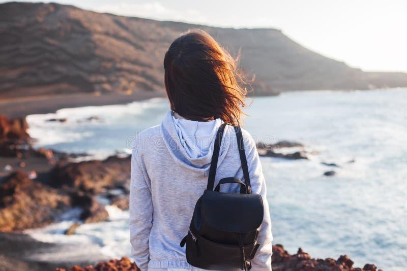 La donna del viaggiatore gode della spiaggia scenica dell'oceano fotografia stock