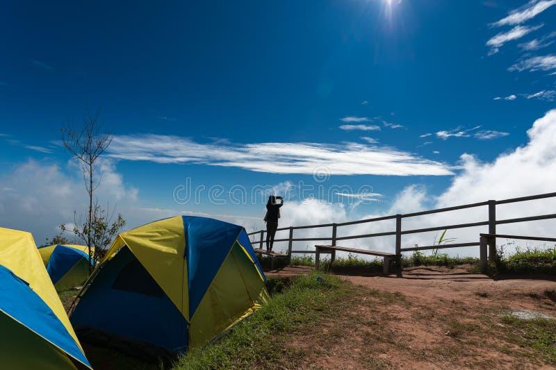 La donna del viaggiatore prende una foto sulla zona di campeggio vicina della montagna immagine stock libera da diritti