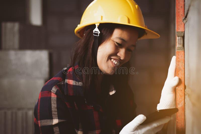 La donna dell'Asia che lavora al sito lavora con felice fotografia stock