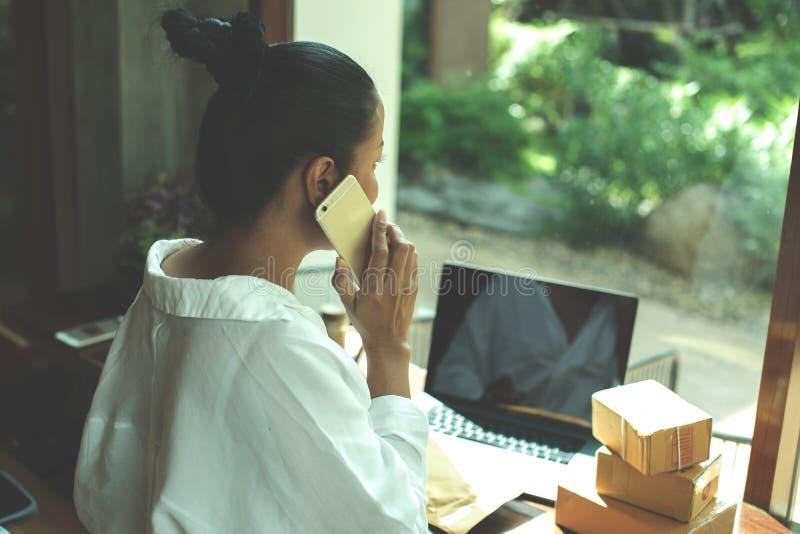 La donna dell'Asia sta tenendo una consegna della scatola di cartone al suo cliente La donna sta controllando al suo cliente, il  immagine stock