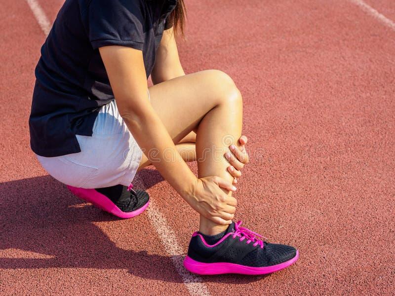 La donna dell'atleta ha ferita alla caviglia, gamba storta durante il trai corrente immagine stock libera da diritti