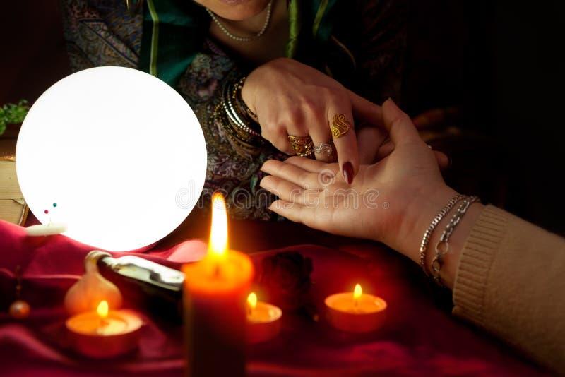La donna dell'indovino indica il suo dito un'altra palma della donna fotografia stock