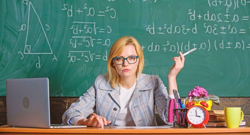La donna dell'insegnante si siede il fondo della lavagna dell'aula della tavola Crei e distribuisca il contenuto educativo Lezion fotografia stock libera da diritti