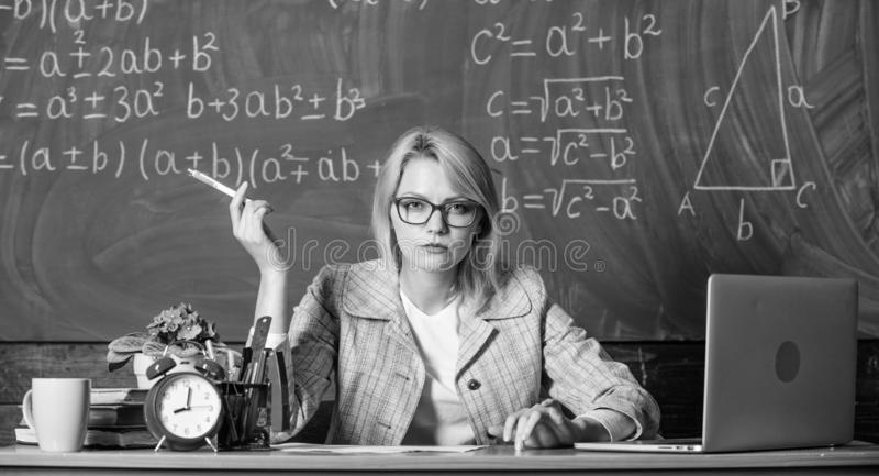 La donna dell'insegnante si siede il fondo della lavagna dell'aula della tavola Crei e distribuisca il contenuto educativo Lezion immagine stock