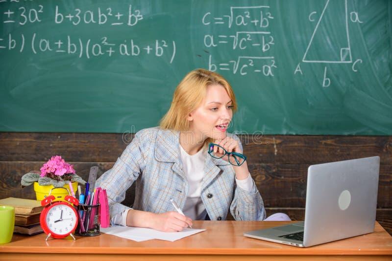 La donna dell'insegnante si siede il fondo praticante il surfing della lavagna di Internet del computer portatile del lavoro dell fotografia stock libera da diritti