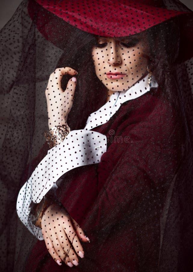 la donna della Alto-società in cappello rosso con il suo velo giù e con le sue armi piegate elegante guarda giù immagini stock libere da diritti