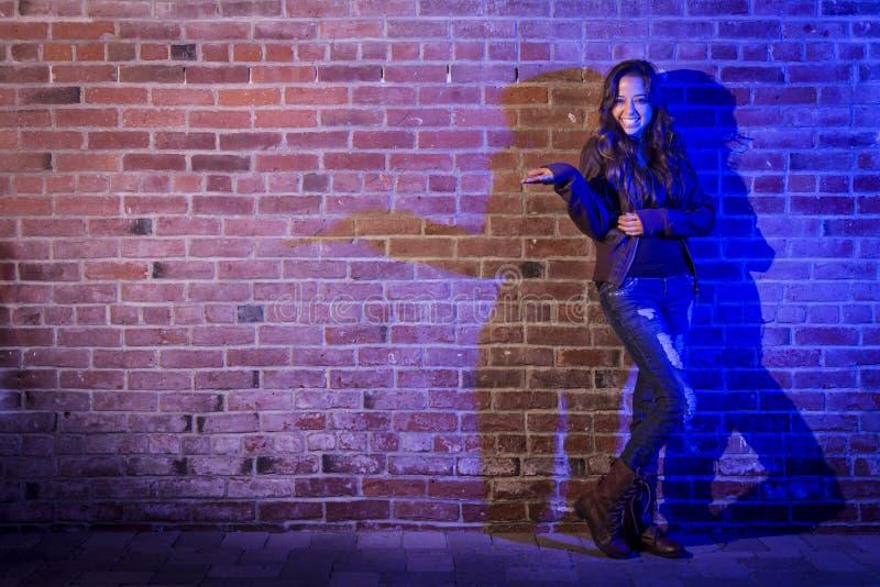 La donna della corsa mista che la tiene distribuisce contro il muro di mattoni immagine stock libera da diritti